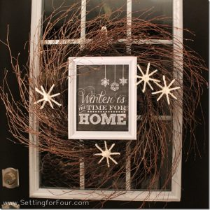 Learn How to MAKE a beautiful DIY Winter Wreath! See this easy winter wreath tutorial and the supply list. This rustic twiggy wreath features a framed winter printable and DIY fluffy white yarn snowflakes to add a cozy touch to your front door!
