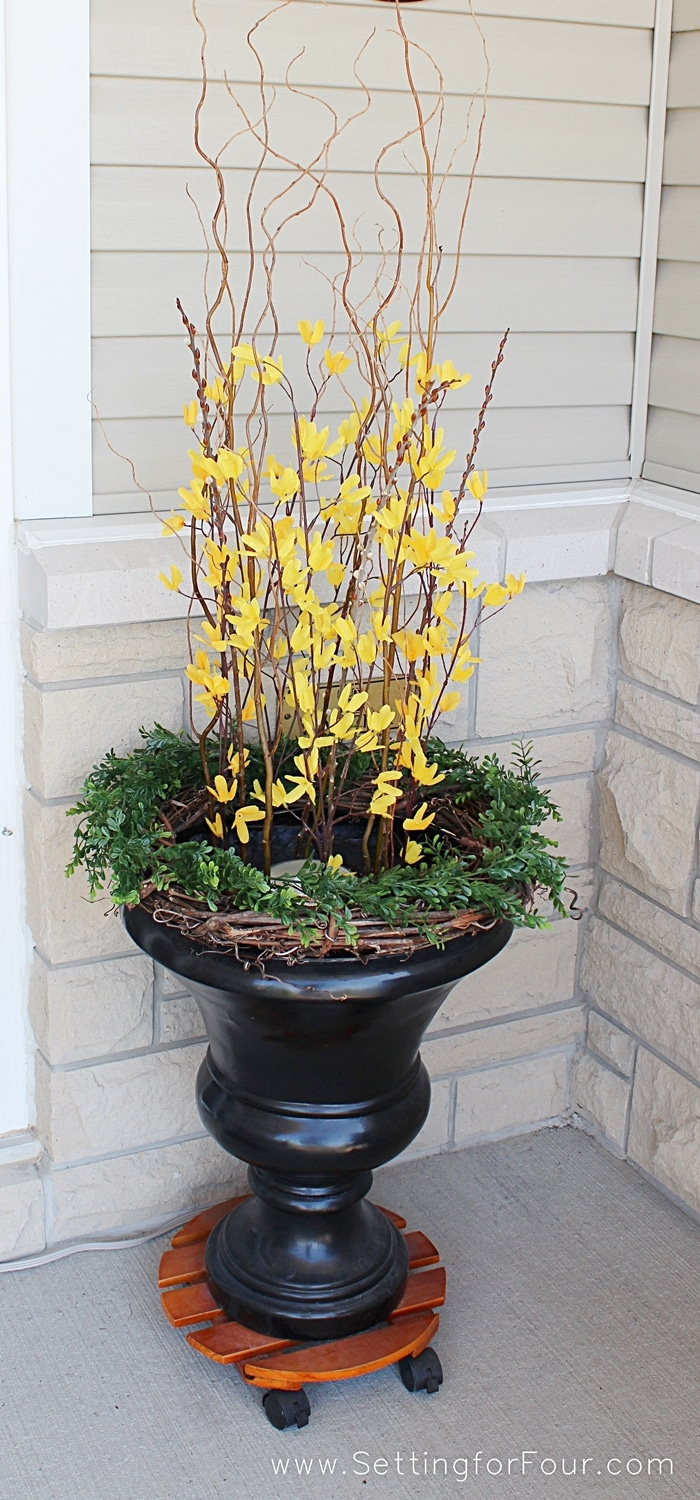 Add curb appeal to your home for Spring by adding an urn or two to your front entryway or front porch! Bright forsythia adds a pop of pretty color. www.settingforfour.com