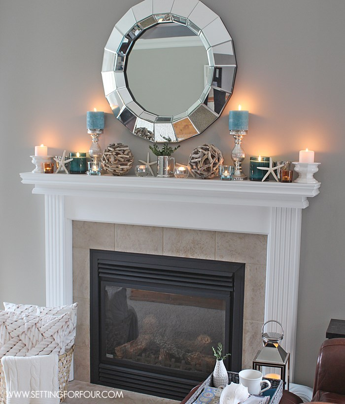 Light the candles at night for a pretty glow! See all the tips on how I decorated this mantel!