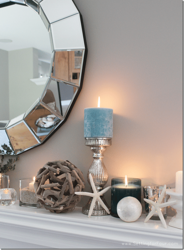 Home decorating ideas and tips: Learn how to decorate a Summer Beach Inspired Mantel with coastal colors and beach style accessories! Add pretty summer decor to your living room mantel with aqua blue candles, starfish, driftwood and capiz shell accents and a statement mirror.