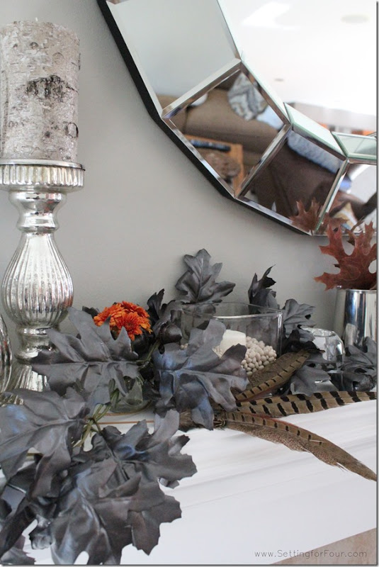 Fall Sparkle and Shine mantel with mercury glass, pheasant feathers, rusty colored mums and a DIY metallic leaf garland!