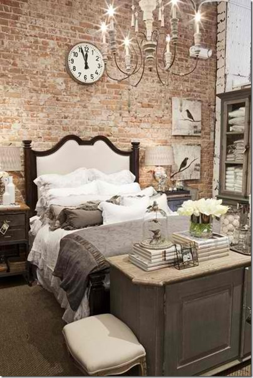 Bedroom with exposed brick feature wall and vintage chandelier.