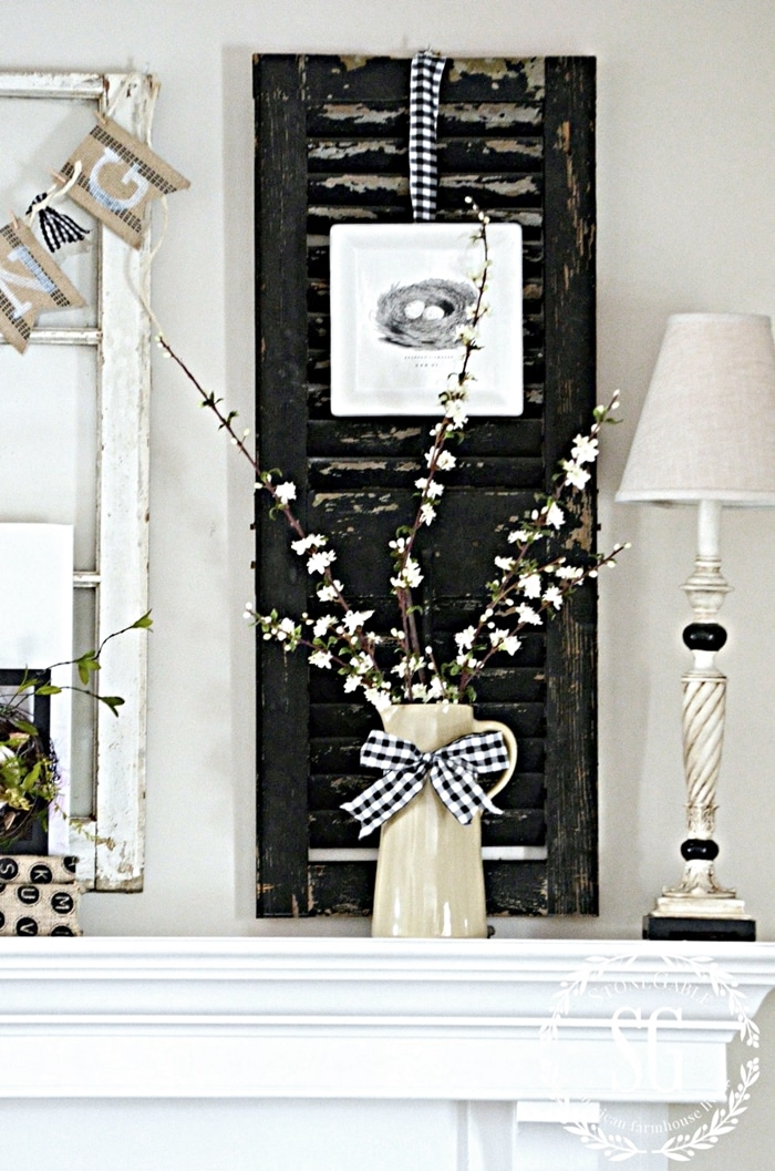 Spring mantel decor with flowers, buralp banner and chippy shutters