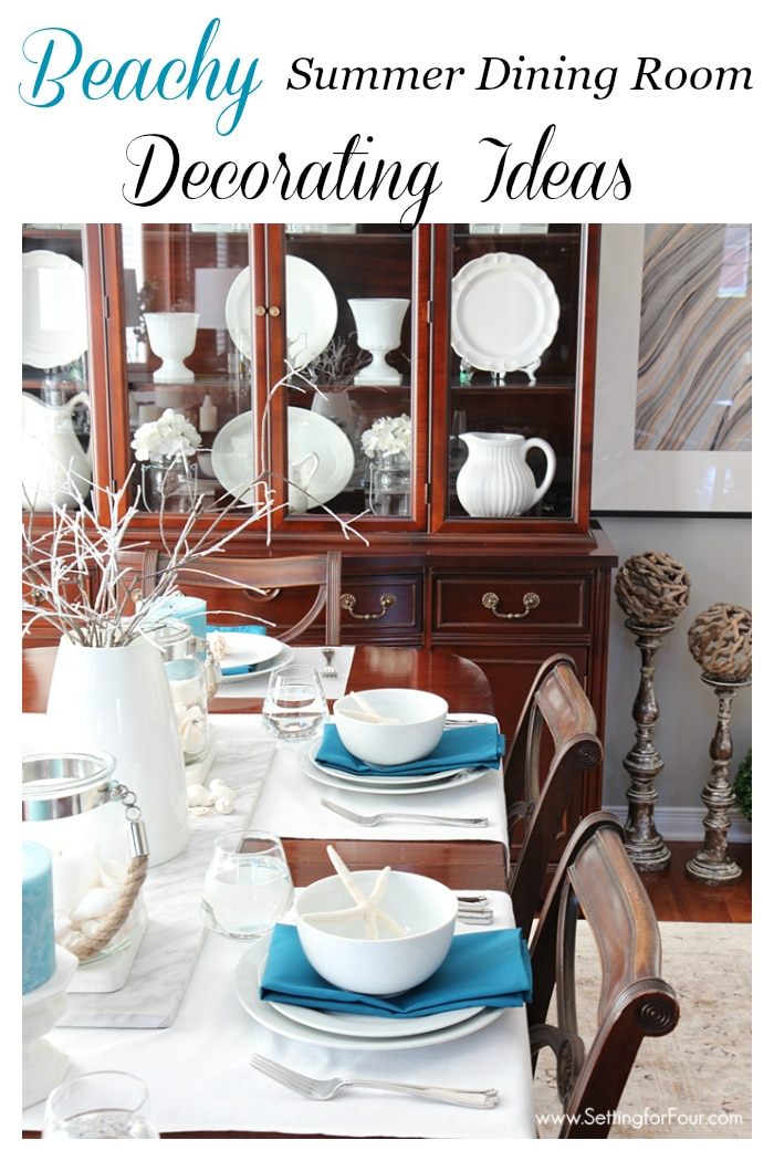See these gorgeous BEACHY dining room decorating ideas and summer tablescape! Birch poles with outdoor cafe lights painted gold, driftwood orbs on top of candlesticks. Ocean blue napkins and candles, lanterns filled with shells, white dishes, white vase filled with white dipped branches and starfish accents at each place setting.