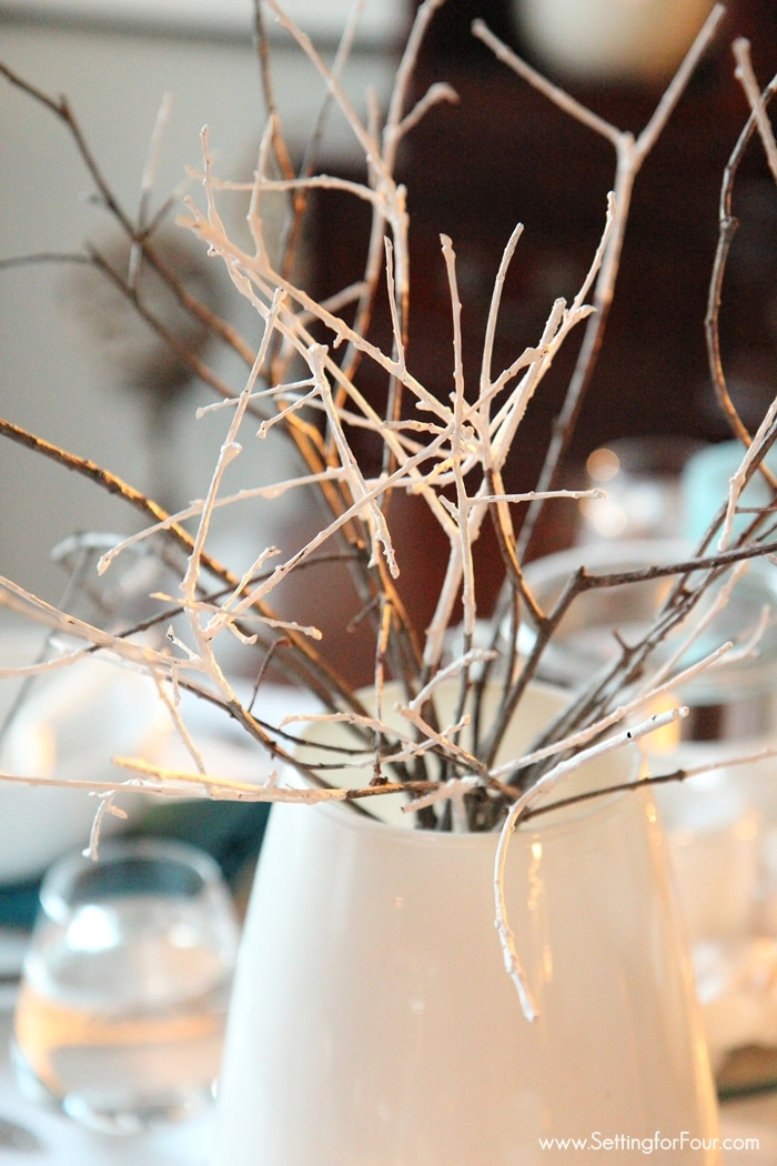 An easy paint dipped branch centerpiece decor idea! See it in my beachy dining room and more EASY beachy decorating tips! www.settingforfour.com