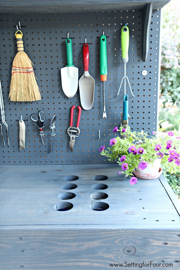 Love to garden? This DIY Pallet Wood Potting bench was so inexpensive to make and has all the bells and whistles! Like bench cleanup holes for excess soil and a cleanup container! See instructions to make and supply list at www.settingforfour.com