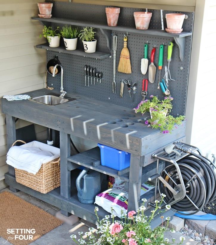 Love to garden? How to make a gorgeous DIY Potting Bench from FREE pallet wood! Has ALL the bells and whistles: a faucet, sink, running water, mounted hose reel, shelves, tool storage, pegboard and more! Free building tutorial, instructions and supply list included. www.settingforfour.com
