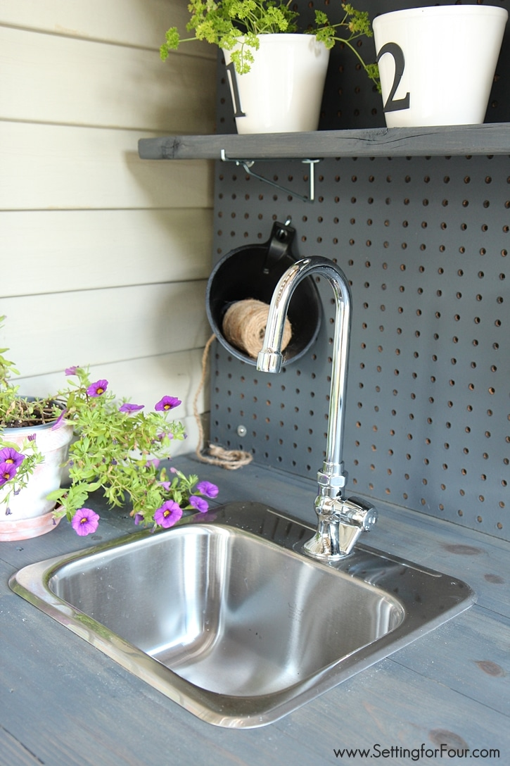 This DIY Potting Bench made from pallet wood has a sink and faucet with water drainage into the flower garden. So clever! www.settingforfour.com