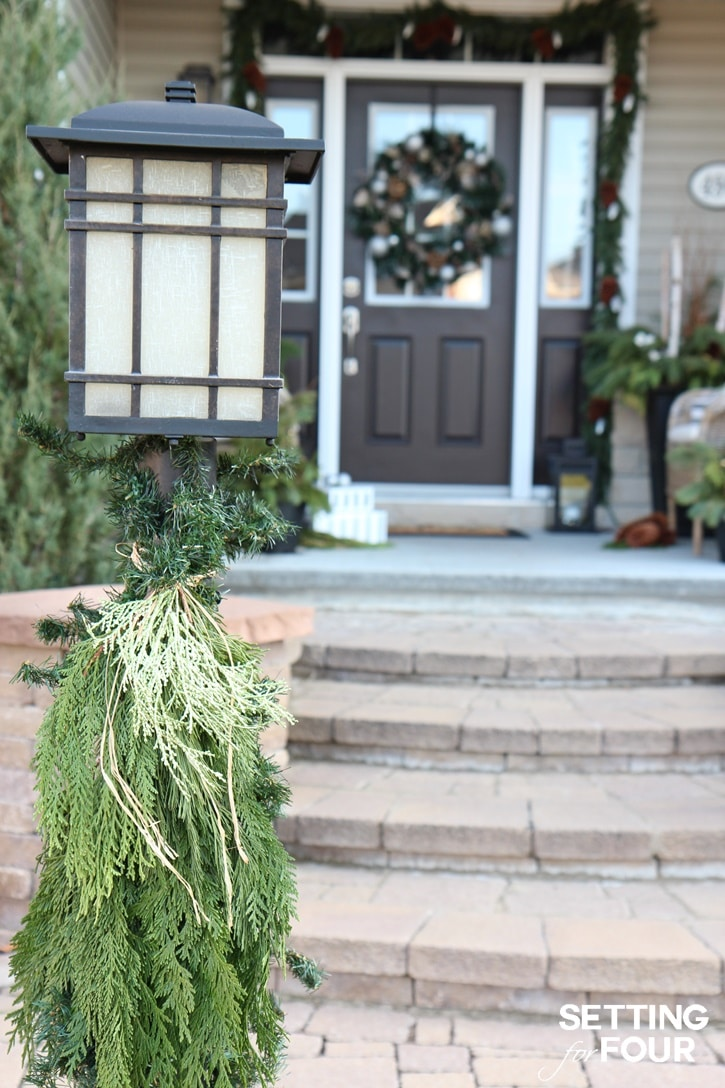 How to add Holiday Cheer Outdoor Christmas decorations to your home: Dress up your lamp post with fresh greenery and raffia! See all of the decor tips at www.settingforfour.com