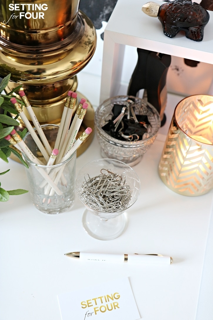 Use a clear water glass to organize and hold pencils and pens - so much prettier than those plastic pen holders! It's simple and it works! See all five of my 10 Minute decorating tips to organize your desk here at www.settingforfour.com