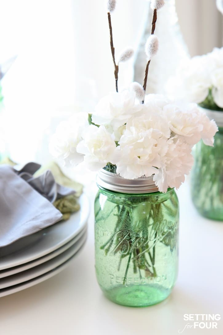 Learn how to make this 10 Minute DIY Floral Mason Jar Idea with pussy willows and carnations: See my budget saving secret to making these gorgeous centerpiece decorations!