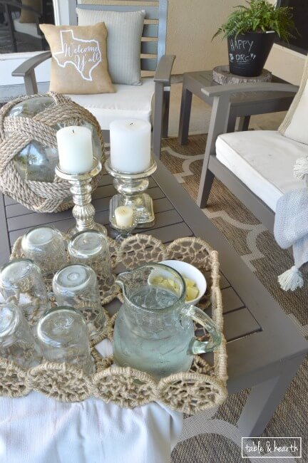 Make neutral colored decor stand out with loads of texture using rope and twine accents plus a woven rug: Rustic Patio Makeover