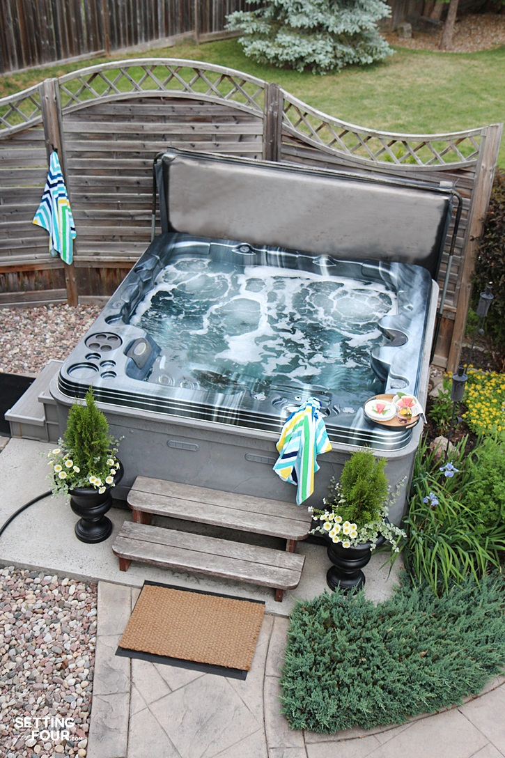 Hot tub in the summer with landscaping plants.