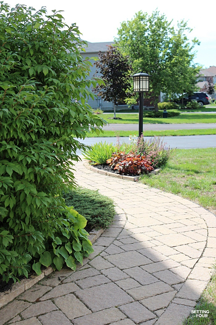Inlaid stone brick path that runs along the front of our home - what a beautiful landscape design.