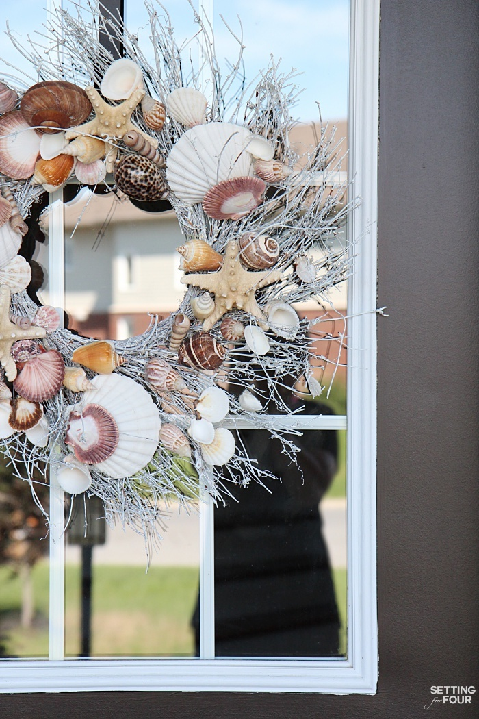 A shell wreath with beautiful starfish, shells and white twigs makes a big statement for any porch!