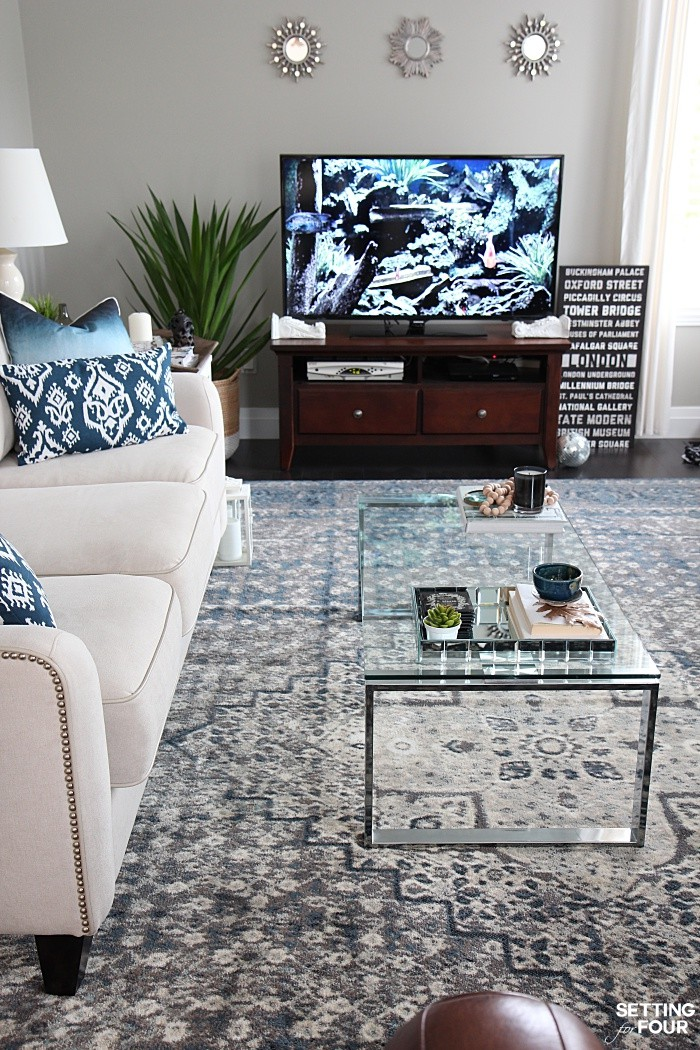Add small decorative mirrors above a TV unit. Living room indigo blue color palette.