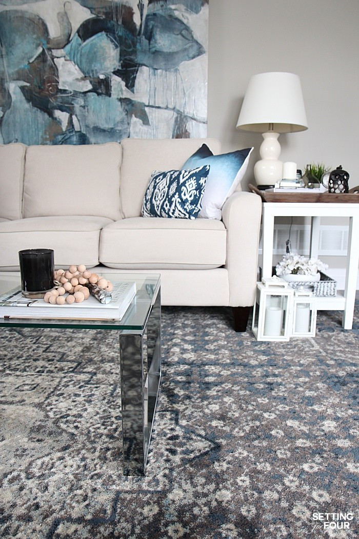 Indigo living room color palette. Pops of indigo blue art, pillows and rug add style to neutral colored walls and furniture.