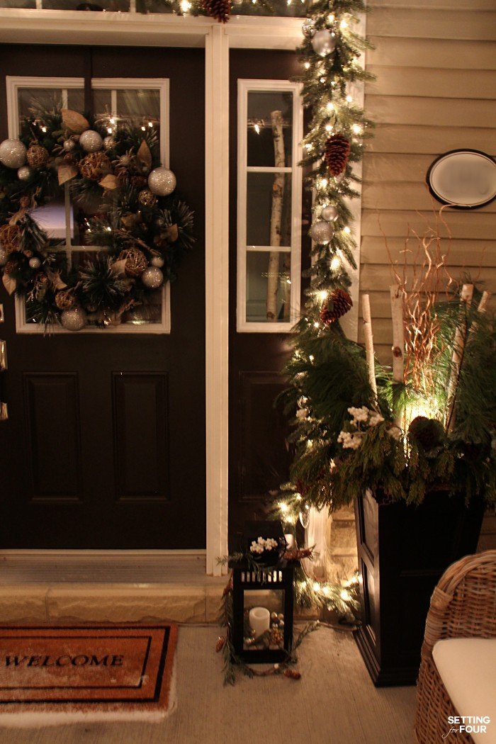 Magical Christmas Lights at Night Home Tour - our front porch with pine garland and Christmas urns lit at night.