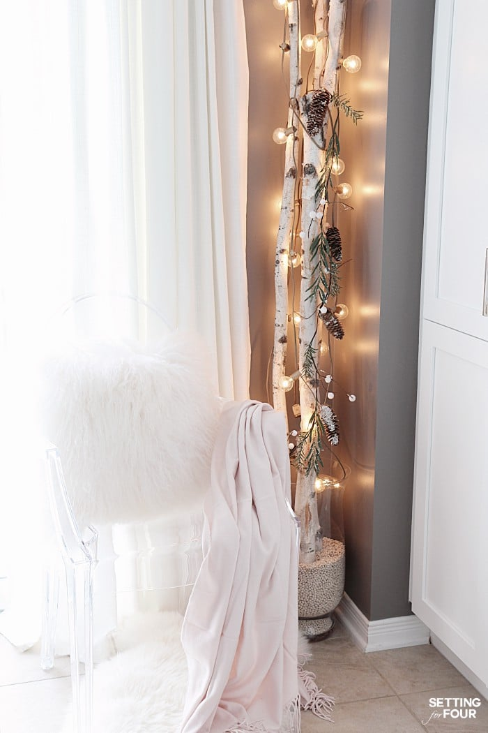 See this quick 10 Minute Winter Decorating Birch Branches Idea! Beautiful birch tree logs in a vase draped with gold globe lights will brighten gloomy winter days and is a great way to decorate a small space in your home! Perfect for a tiny house, apartments and condos!