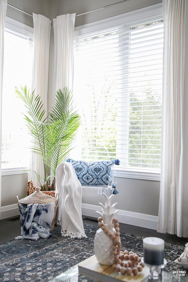 Living room with white drapes, ghost chair, shibori pillow, palm tree, lidded basket, blue area rug.