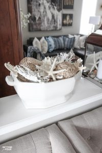 Learn how to make a Pretty Faux Coral & Starfish Coastal Summer Centerpiece that's quick and easy to put together! This Pottery Barn inspired centerpiece is the perfect table top, coffee table and bookshelf decor for parties, weddings or to update your home for summer. If you love coastal decor and collect shells you'll love this beautiful sea inspired arrangement!