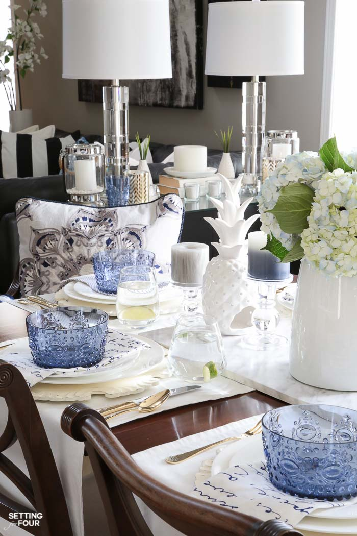 Blue and white napkins, blue bowls, white ceramic pineapple decor, blue hydrangea centerpiece layered together for a summer tablescape.
