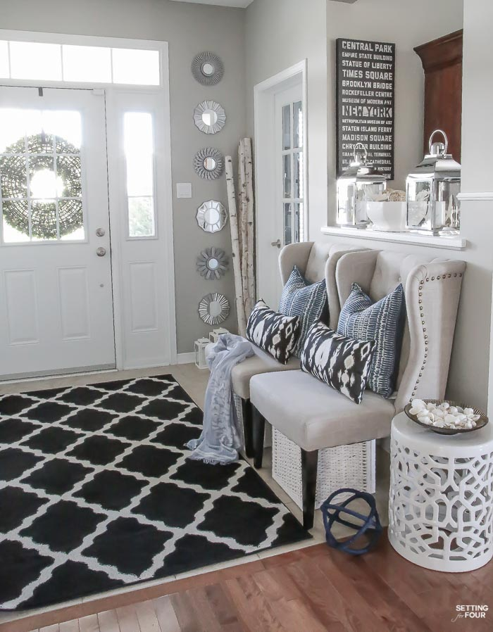 Summer home tour and summer decorating ideas. Decorating with indigo blue, black and gray color scheme. Foyer with wingback chairs, indigo shibori pillows, ikat pillows, garden stool, sunburst mirror gallery wall, birch vases, silver candle lanterns and trellis area rug