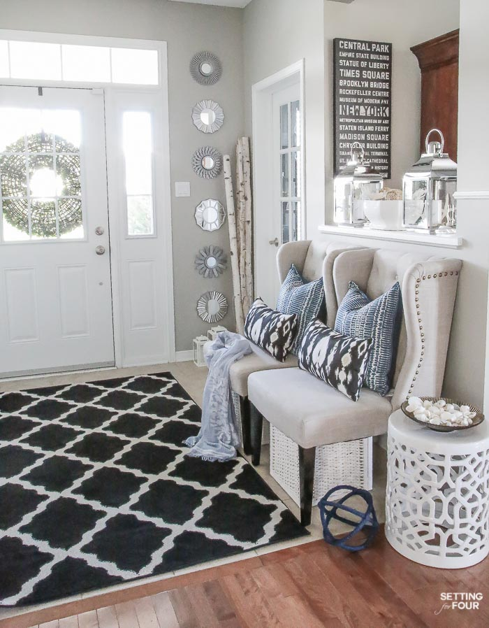 Need some new decorating ideas? See my foyer decor ideas including my indigo blue, black and gray color scheme, make this DIY coastal centerpiece, lanterns, garden stool, seating, area rug and pillow accents.