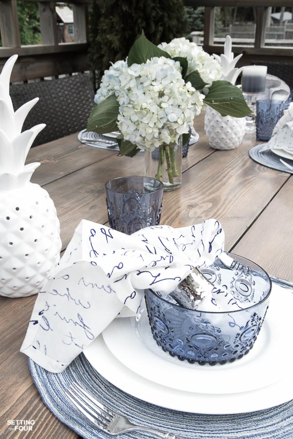 Summer outdoor dining. Table setting in blue and white. Hydrangea centerpiece, white ceramic pineapple decor.