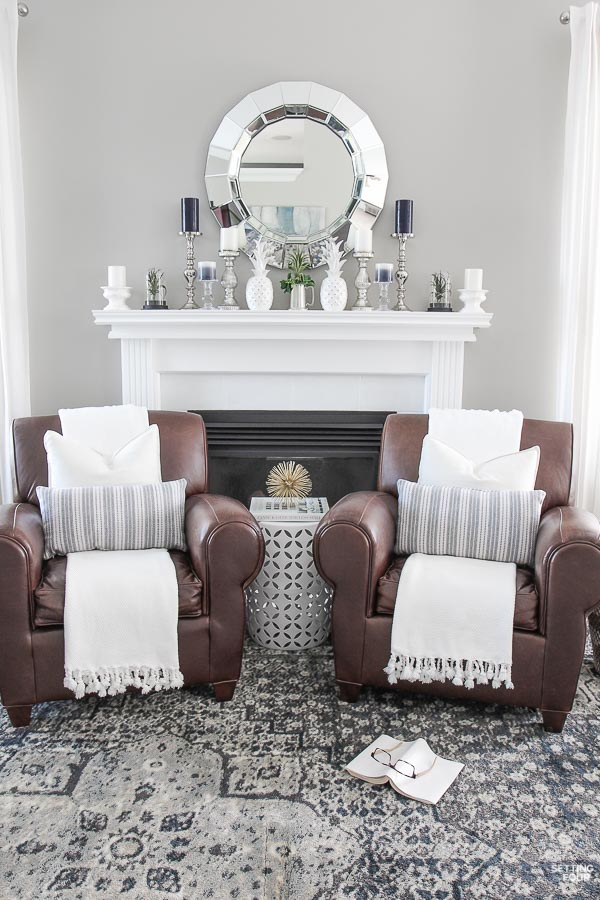 Living room with blue and gray vintage area rug, Pottery Barn leather club chairs, tasseled throws, garden stool, painted fireplace mantel, faceted mirror, mantel decor ideas.