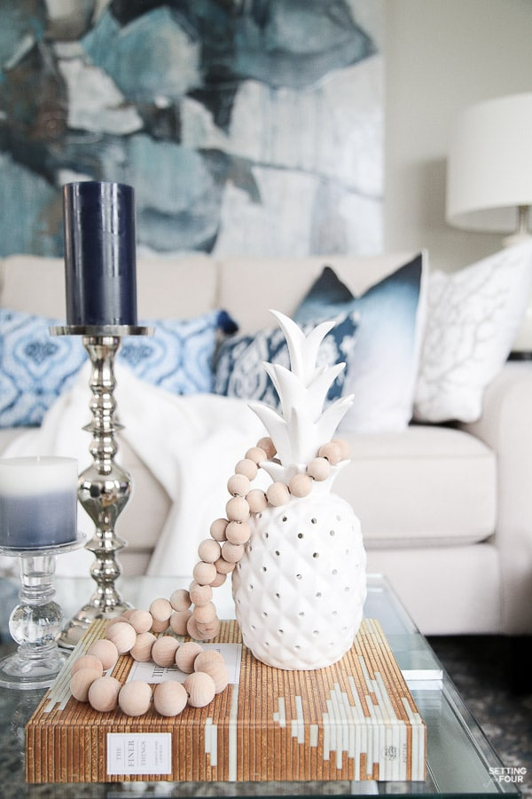 Summer decor ideas and design blogger's home tour. Indigo black and gray color scheme. Abstract art, indigo pillows, cream sofa, white pineapple, prayer bead garland and coffee table vignette.