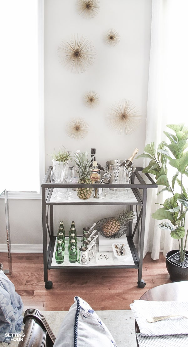 Bar cart decorated with marble shelves, barware, cocktail drinks, and wall art idea.