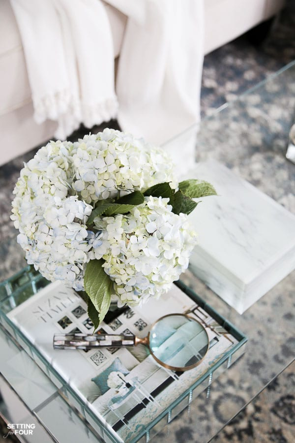 Coffee table styled with tray, hydrangea bouquet, coffee table books.