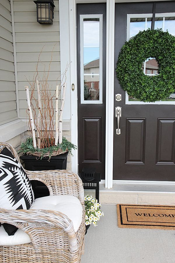 Summer home tour and summer decorating ideas. Front door wreath, urn planters with birch, wicker chairs, blue colored plants.