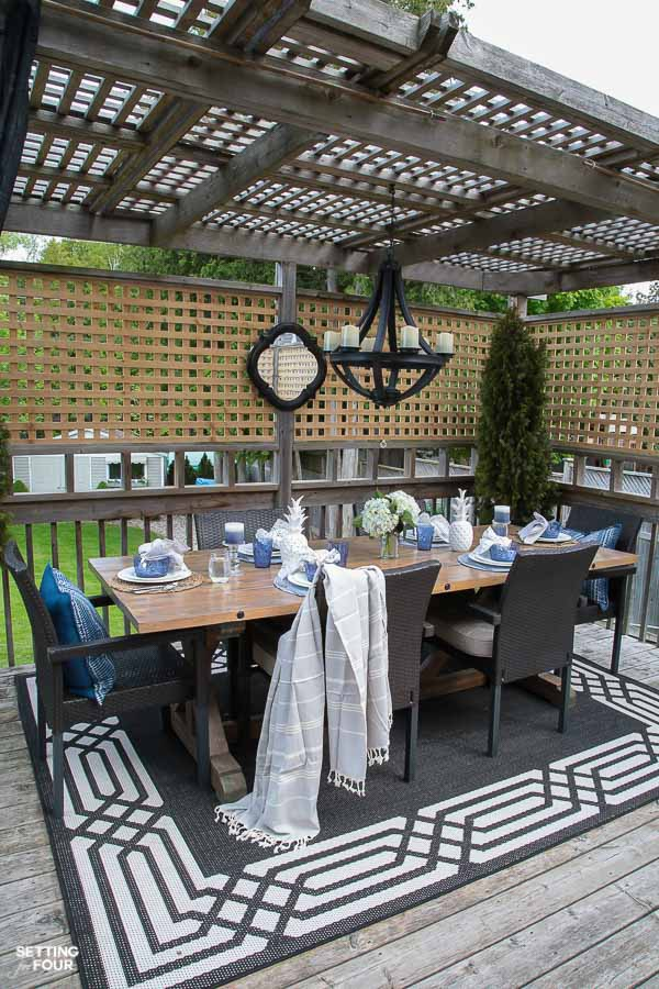 Outdoor gazebo idea for summer. DIY wood Dining table, outdoor chandelier, outdoor mirror, outdoor area rug, wicker stackable chairs, blue and white table setting, planters.