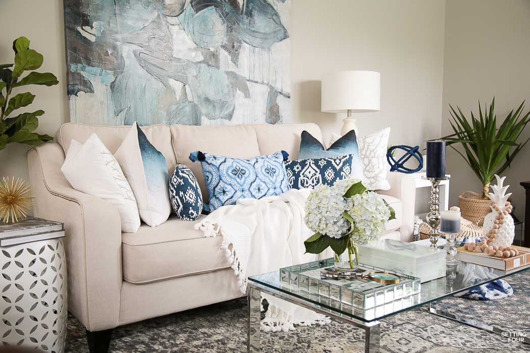 Summer decor ideas and design blogger's home tour. Indigo black and gray color scheme in living room. Abstract art, indigo pillows, cream sofa, white pineapple, prayer bead garland and coffee table vignette.