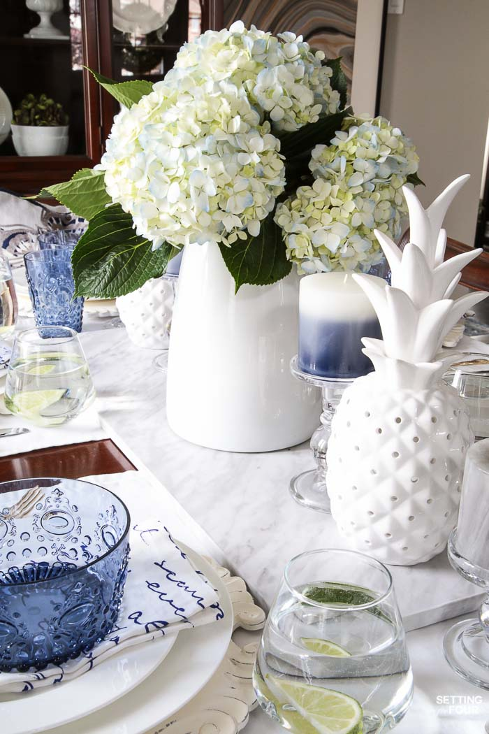 Blue and white napkins, blue bowls, white ceramic pineapple decor, blue hydrangea centerpiece layered together for a summer tabletop idea.
