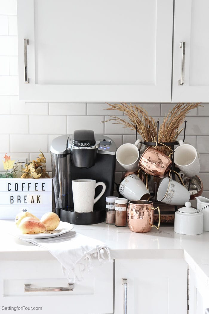 How to create an elegant kitchen coffee bar for Fall that's perfect for family as well as entertaining friends and guests! See all the details: This countertop coffee station decorated with fall foliage is a pretty way to display your coffee pot, mugs, coffees, coffee flavorings and teas!