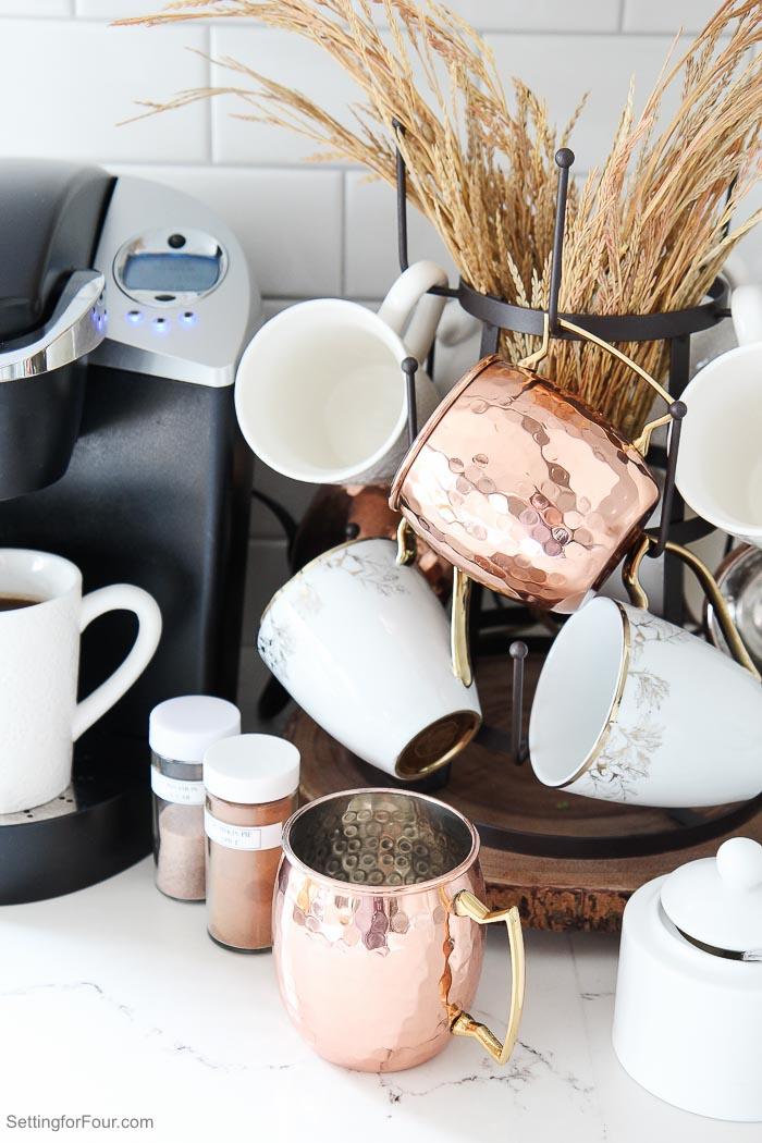 Coffee Station Decor ideas with Keurig machine, white coffee mugs, copper mule mugs, tiered mug rack, wood slice trivet and coffee toppings.