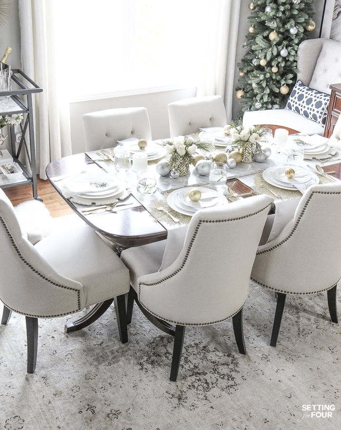 Learn how to create this Elegant Gold And White Christmas Tablescape that's quick and easy to put together! Give white dishes a festive look with white, silver and gold Christmas ball ornaments and beautiful DIY white rose and pine winter centerpieces. This Christmas table decor is perfect for holiday dinner with the family, big dinner parties and winter weddings too!