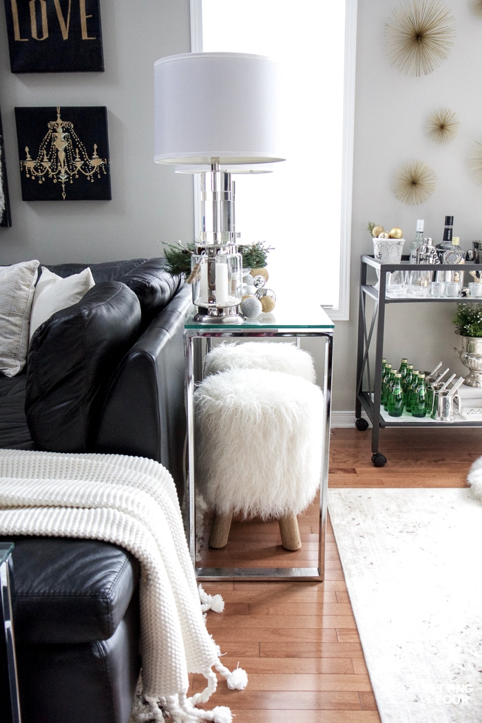 See my Glam Black, White and Gold Family Room Decor Ideas! I kept my holiday decor simple this year - a mini flocked Christmas tree with gold and silver ornaments, some faux pine greenery and bowls of metallic Christmas balls keep this space looking light and bright but festive too! See my entire family room here! Leather sectional sofa, poufs, shag area rug, crystal table lamps, chunky knit throw blanket, black and white color palette, faux fur pillows, metallic wall art.