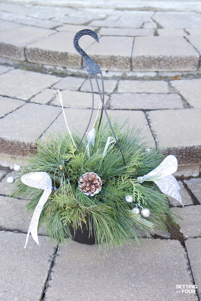 How to turn a basic Christmas hanging basket into a stunning outdoor Christmas urn planter for your front door! Add curb appeal to your home in a jiffy!