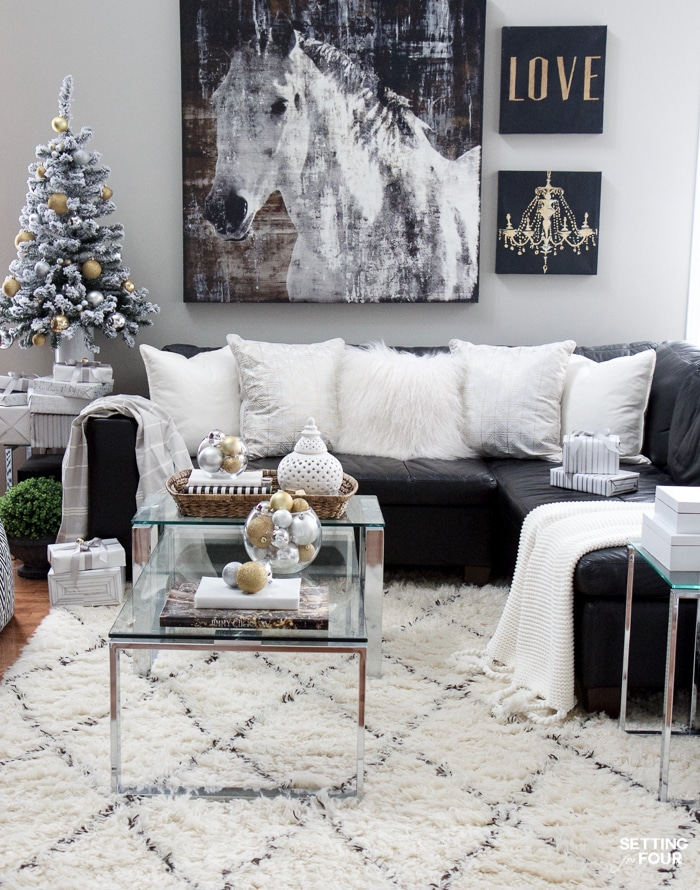 See my Glam Black, White and Gold Christmas Family Room Decor Ideas! I kept my holiday decor simple this year - a mini flocked Christmas tree with gold and silver ornaments, some faux pine greenery and bowls of metallic Christmas balls keep this space looking light and bright but festive too! See my entire family room here! Leather sectional sofa, poufs, shag area rug, crystal table lamps, chunky knit throw blanket, black and white color palette, faux fur pillows, metallic wall art.