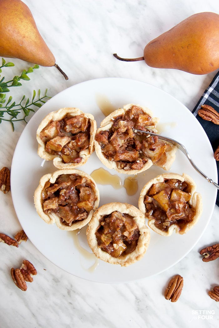 Make this quick and easy Cinnamon Pecan Pear Tartlets recipe with delicious maple syrup, ready to bake in just 20 minutes! Add yummy maple cream to these miniature pies as a topping. NO handmade pie crust required: This recipe turns store bought pie crust into these beautiful ruffled tartlets for easy baking!