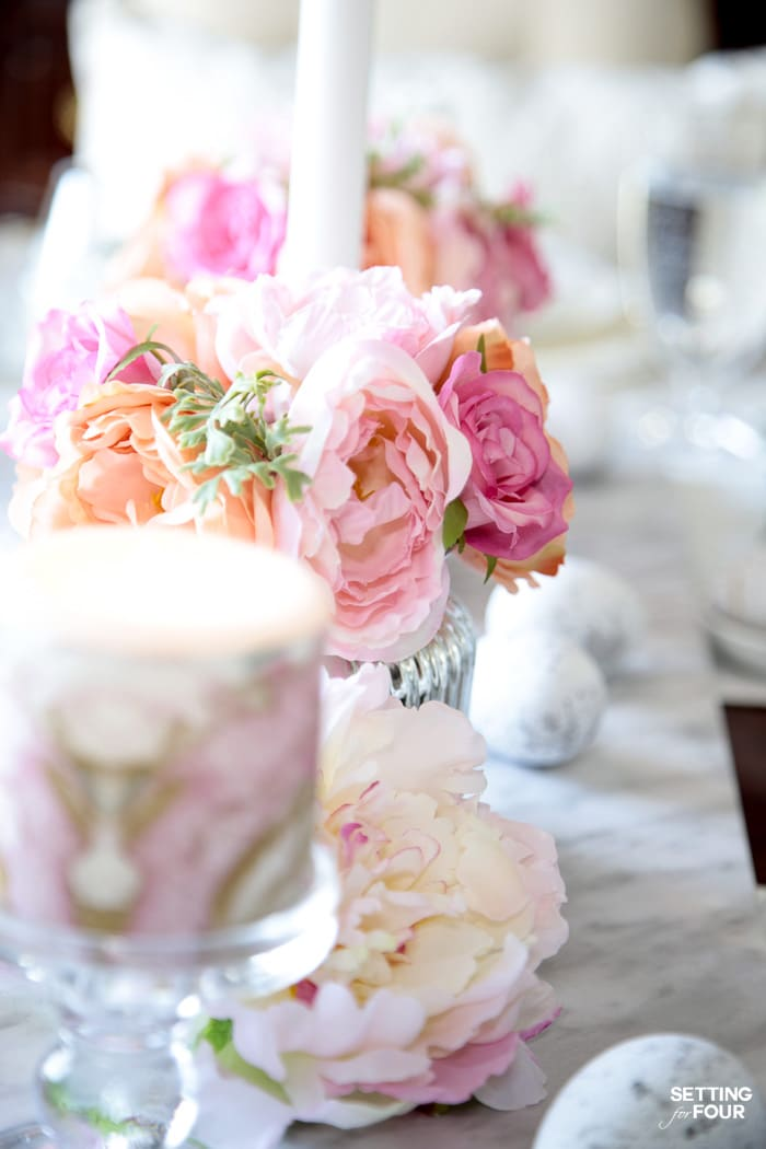 Easter tablescape: pink floral centerpieces and pink marbled candles with a marble runner.