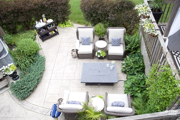 Patio seating area with outdoor furniture, bar cart, fire table, container flowers and landscaped back yard.