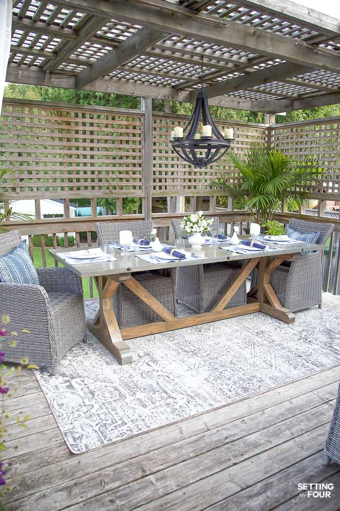 Outdoor pergola dining area with wood trestle table and wicker chairs