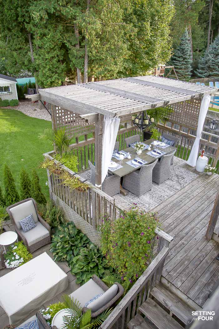Our Back Deck Pergola Dining Area - see our DIY trestle table, outdoor dining chairs, area rug and more! #outdoor #pergola #deck #decor #furniture #diy #table #arearug #landscaping #planters
