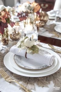 An elegant gold and white Thanksgiving tablescape. Table decorating tips and place setting ideas. #thanksgiving #entertaining #tabletop #napkinfold #pumpkin #decoration #holiday #dinnerparty