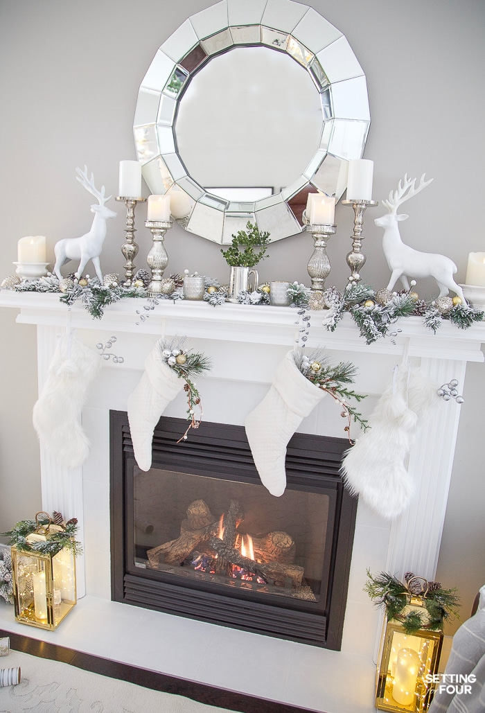 Simple white fireplace mantel with mirror decorated for Christmas with lanterns and twinkle lights #christmasmantel #twinklelights #christmaslights #mirror #fireplace #lanterns